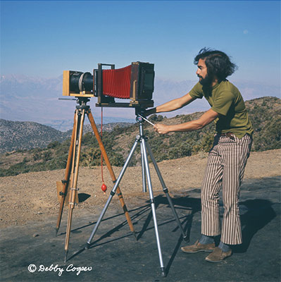 "Photographer Ed Cooper with special telephoto set-up for large format. An 8x10 Eastman Kodak view camera was attached to a 36"" Dallmeyer lens (former aerial spy lens). Two tripods were required to support this set-up. Ed Cooper installed a Packard shutter triggered by a red bulb. September 1970 in the White Mountains looking towards the Sierra Nevada. Copyright Debby Cooper Photo. California."
